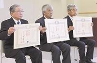 勲記を手に左から沼津氏、木村氏、佐藤氏