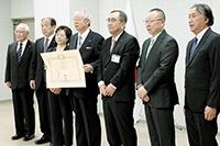 町の関係者と記念写真に収まる井上夫妻(左から3、4人目)
