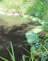 網袋に入れ水面に浮かべられた大麦のワラ