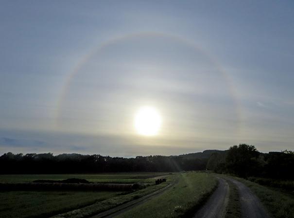 作品名『大きな暈』北見市・男性 10月5日午後3時40分ころ、北見市豊地の無加川堤防道路で撮影しました。西に沈む太陽に大きな暈(かさ)がかかり、七色に輝いて虹のようにきれいでした。