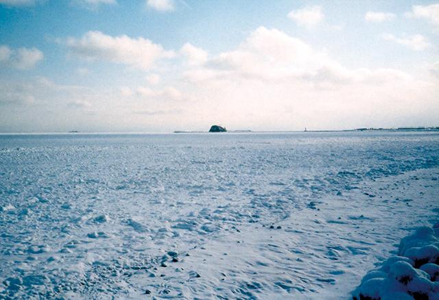 作品名『流氷と帽子岩』網走市・雲好き とても寒い日の流氷です。寒々しい空と雲。ずっと向こうに小さく見えるのは帽子岩。何も言わず寒さに耐えている…そんな光景です。