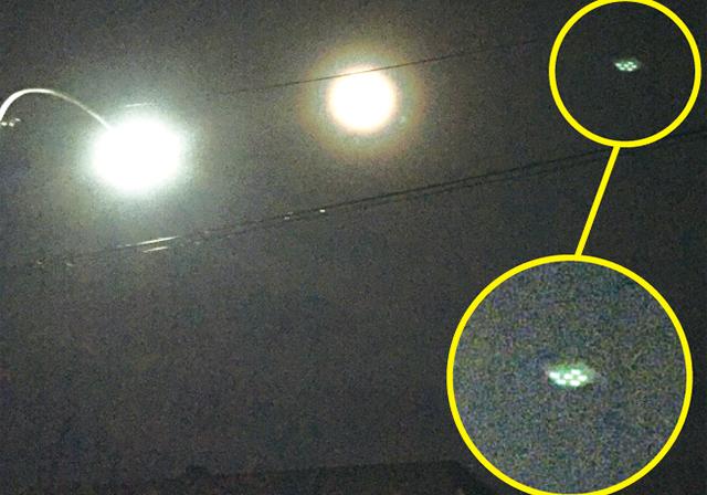 作品名『未確認飛行物体?』津別町・豆太郎月に光の加減で輪がついてるように見えてめずらしく思い住宅の屋根越しに写真を撮ったら、不思議なモノが写っていました。左が街灯で中央が月。右側の6つの光の集合体は何?屋外で撮ったのでガラス越しによる照明の反射ではないと思います。