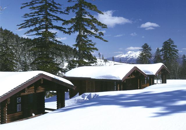 作品名『藻琴山キャンプ場にて』一町民 夏の賑わいとは打って変わって、山小屋は冬の長い眠りについている。時折スキー登山者が通り過ぎる。雪面の縞模様は、西に傾いた日差しが映すエゾマツの長い影。静かに静かに、俗塵から遠ざかるように時が流れる(2月下旬撮影)。